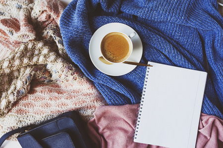 shopping list for winter sale with cup of coffee and cozy stylish sweaters