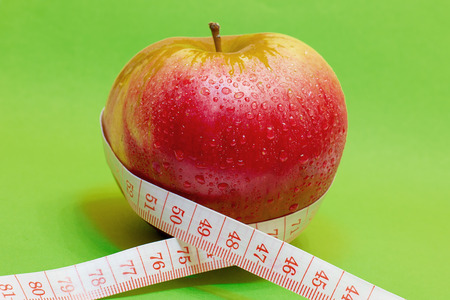 apple and measuring tape on green background photo