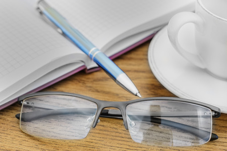 wealth concept: glasses pen on the table and pads Stock Photo