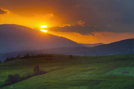 extreme angle: sunset in the mountains in the foreground field and tree nature Stock Photo