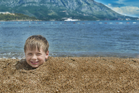 head in the sand: Boy buried in sand on the sea behind head smiling cloudy sky Stock Photo