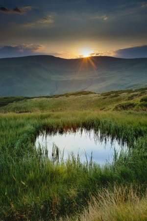 solar array: Lake in the mountains, solar reflections, Svydovets array sunset over the mountains Stock Photo