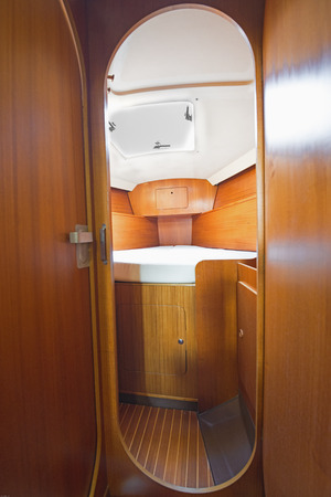 stateroom: room in the boats cabin in a sailboat, a small cozy bedroom, wooden walls,