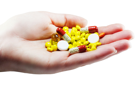 doctor holding pills: female palm colored and white pills isolate