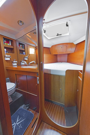 stateroom: room in the boats cabin in a sailboat, a small cozy bedroom, toilet, wooden walls,