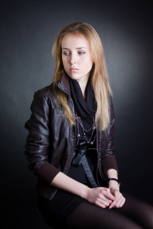 grieved: Young beautiful sad woman sits and looks toward  Dark background