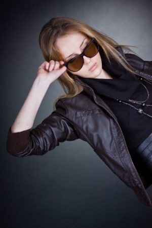 grieved: Beautiful sad blonde woman with sunglasses  Dark background Stock Photo