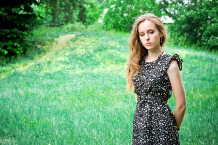 grieved: Sad woman stays in a forests meadow Stock Photo