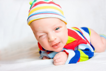 Funny Newborn Baby Lies Lie on stomach, smiles and winks  photo