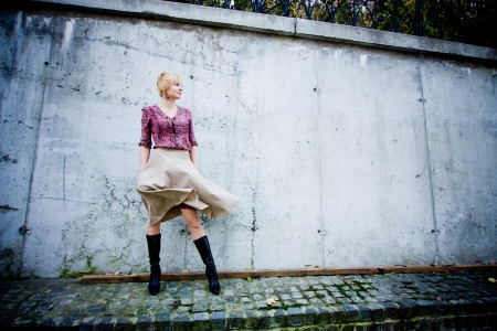 Fashion look with skirts and blouse in the city. Windy. photo
