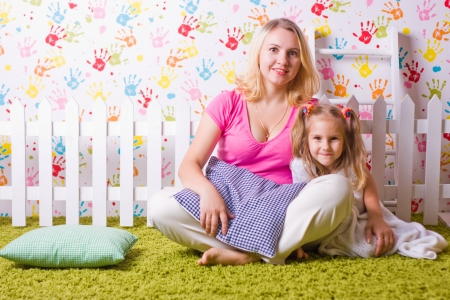 green carpet: Happy mother and daughter sit on the green carpet