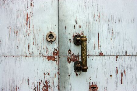 Handle and keyhole on white cracked wooden door