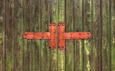 Metal elements with rivets on wooden green cracked door Imagens