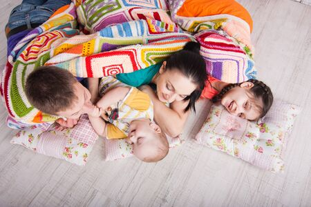 Happy family lie on the floor under colorfull blanket and laught. Indoor photo shot