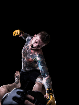 opponent: Aggressive MMA fighter punching opponent on the ground on black background