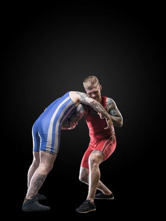 wrestlers: Two young freestyle wrestlers in red and blue uniform wrestling isolated on black background