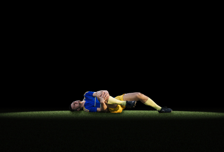 laying forward: Professional young football to experience pain lying on grass on black background