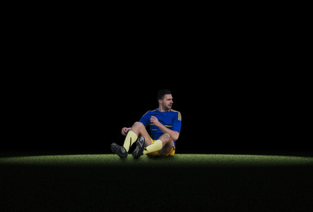 lying forward: Caucasian young soccer player sitting on green grass isolated Stock Photo