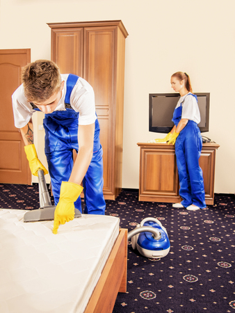 cleaning team: Cleaning team in blue uniform working in room in morning Stock Photo