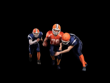 crouches: Young football players with a blue and red uniform on black background