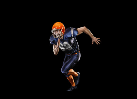 crouches: Professional american football player in action isolated on the black background