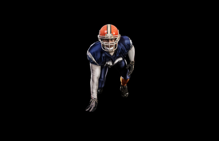 crouches: Professional american attacking football player in blue uniform isolated Stock Photo