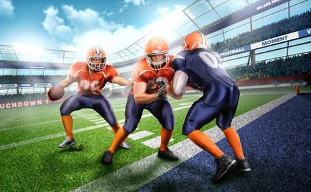 Young and strong american football players in the action on stadium on green grass Stock Photo