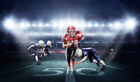 Young football players with a blue and red uniform in a stadium with fans Stock Photo