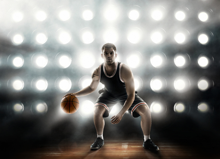 basketball player on floodlight background and parquet with ball Stock Photo