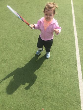 pretty young tennis player with a racket on a tennis grass court, childrens tennis training