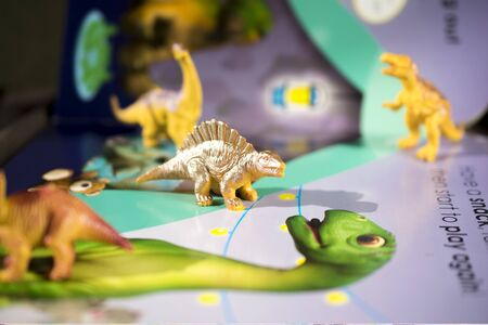 a fairy tale about dinosaurs in a book with text and toys in . Banco de Imagens