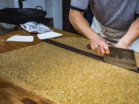 Person slicing chinese sesame peanut brittle snack