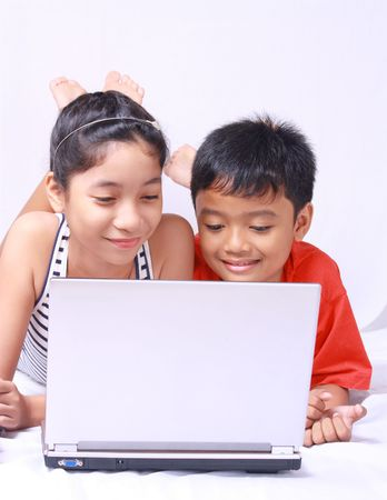 young asian kids enjoying and sharing a laptop computer 版權商用圖片