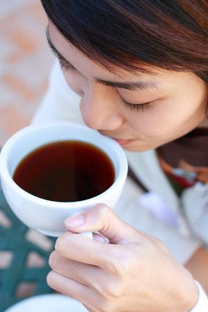 women holding cup: asian lady drinking a cup of coffee