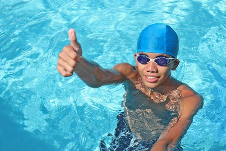 young asian swimmer making a thumbs up for victory