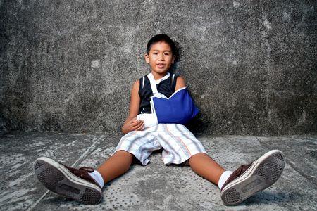 luxacion: un joven con una cinta azul en brazo roto  Foto de archivo