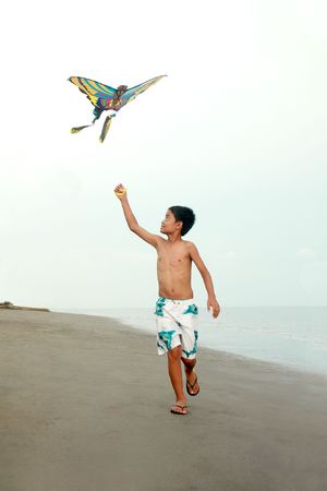 young asian boy flying a kite at the beach