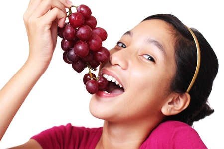 Young asian teenager eating a bunch of grapes. White background. 版權商用圖片