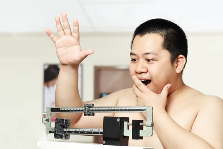 kilograms: young asian fat man on a weighing scale Stock Photo
