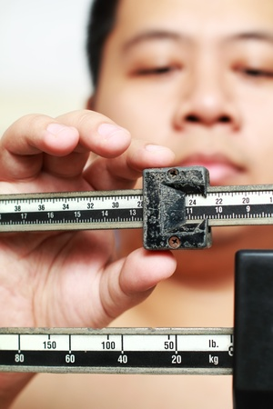 Man measuring weight on an old weighing scale