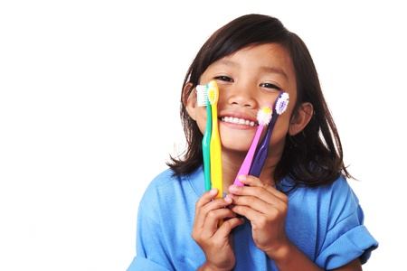 Young girl showing toothbrush and her white teeth
