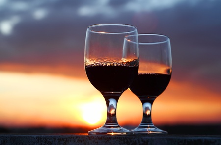 Two glasses of red wine silhouette in sunset. Stock Photo - 11399605