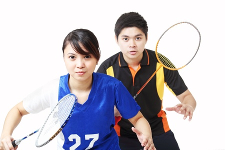double game: Young athletes in badminton doubles.Isolated in white background. Stock Photo