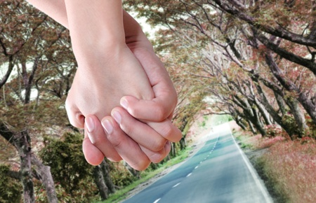 close up image: Close up image of lovers hand while walking on the road.