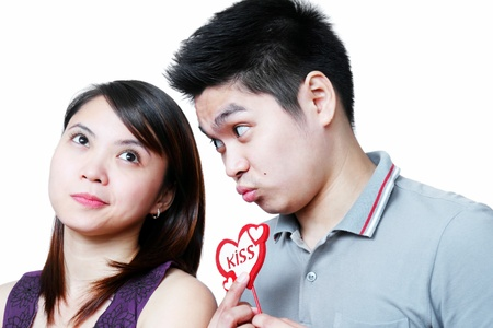 requesting: Young man requesting a kiss from girlfriend. Stock Photo