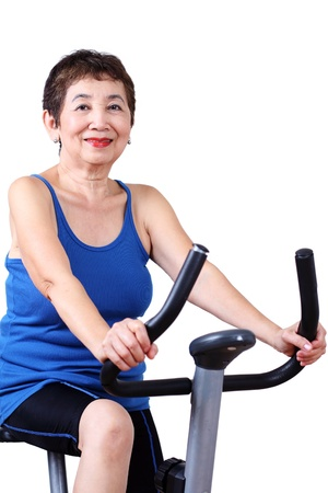 Fit senior woman exercising on a stationary bicycle. photo
