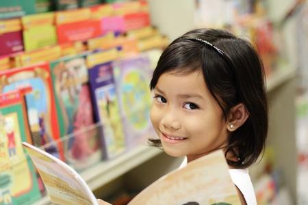 bibliotecas: Feliz chica asi�tica en la biblioteca. Foto de archivo