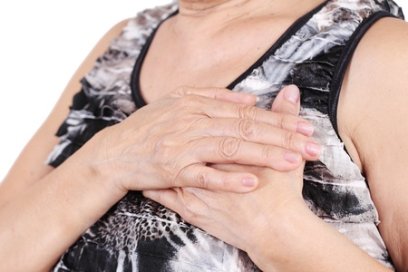 Close up of a senior womans hand holding her chest. photo