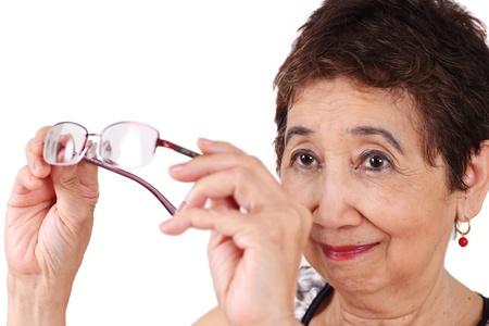 poor eyesight: Senior woman with poor eyesight checking her eyeglasses.
