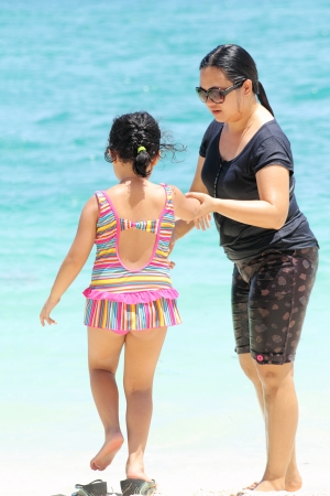Mother and child walking at the beach. Stock Photo - 14266920